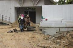 Asiatisk kvinnaarbetare som lastar av sand för konstruktion Arkivbilder