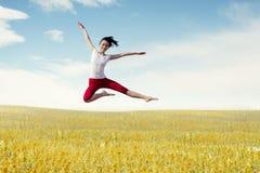 Asiatisk kvinnaballerina som gör ett stort hopp på äng Royaltyfri Foto