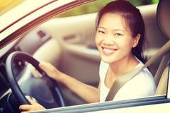 Asiatisk kvinnachaufför som kör en bil Royaltyfria Bilder