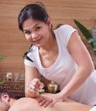 Asiatisk kvinnadanandemassage till en man royaltyfria bilder