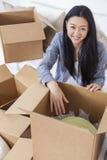 Asiatisk kvinnaflicka som packar upp askar som flyttar huset Royaltyfria Foton