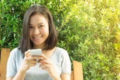 Asiatisk kvinnahand genom att använda mobiltelefonen i trädgård med kopieringsutrymme Arkivbild