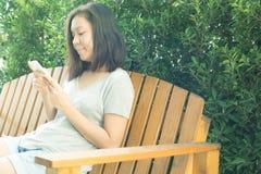 Asiatisk kvinnahand genom att använda mobiltelefonen i trädgård med kopieringsutrymme Royaltyfria Foton