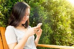 Asiatisk kvinnahand genom att använda mobiltelefonen i trädgård med kopieringsutrymme Arkivfoton