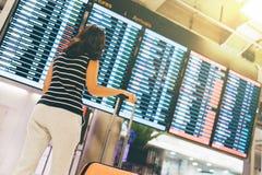 Asiatisk kvinnahandelsresande som ser informationsskärmen om flyg i en flygplats, ett hållande resväska-, lopp- eller tidbegrepp Royaltyfri Fotografi