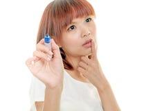 Asiatisk kvinnahandstil med den blåa markören på imaginärt bräde Fotografering för Bildbyråer