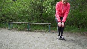 Asiatisk kvinnalöpare för sund livsstil som sträcker ben, innan att köra arkivfilmer