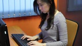 Asiatisk kvinnamaskinskrivning på datoren