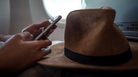 Asiatisk kvinnapassagerare som använder apparattelefonen under det inre flygplanet för flyg royaltyfri fotografi