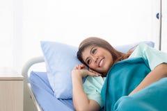 Asiatisk kvinnapatient som använder mobiltelefonen på säng som medges i sjukhus arkivfoton