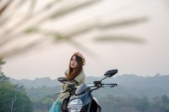 Asiatisk kvinnaridningmoped i tropiskt fält arkivfoto