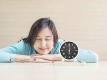 Asiatisk kvinnasömn, vid legat på skrivbordet med den lyckliga framsidan i vilotid från läseboken med klockashow tiden i 6 klocka royaltyfri foto