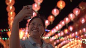 Asiatisk kvinnaselfie med smartphonen mening lyckligt Härliga lyktor BG stock video