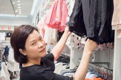 Asiatisk kvinnashopping i modekläderlager Arkivfoto