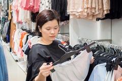 Asiatisk kvinnashopping i modekläderlager Fotografering för Bildbyråer