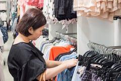 Asiatisk kvinnashopping i modekläderlager Royaltyfria Bilder