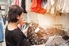 Asiatisk kvinnashopping i modekläderlager Arkivfoton