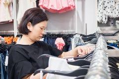 Asiatisk kvinnashopping i modekläderlager Arkivbilder