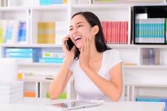 Asiatisk kvinnastudent som är lycklig med telefonen Arkivbild