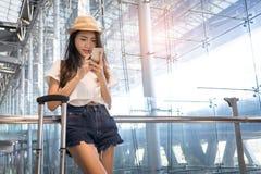 Asiatisk kvinnatonåring som använder smartphonen på flygplatsen Royaltyfri Bild