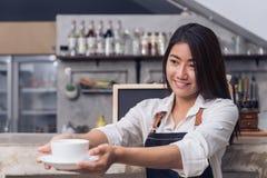 Asiatisk kvinnlig baristahåll per koppen kaffe som tjänar som till hennes kund med leende som omges med stångräknarebakgrund Arkivbilder