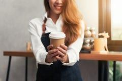Asiatisk kvinnlig baristahåll per koppen kaffe som tjänar som till hennes kund med leende som omges med stångräknaren Arkivbilder