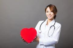 Asiatisk kvinnlig doktor med hjärta royaltyfria foton