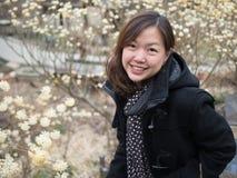 Asiatisk kvinnlig i det svarta omslaget som ser och ler till kameran Royaltyfri Bild