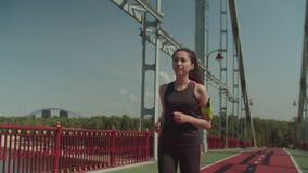 Asiatisk kvinnlig jogger som kör på den fot- bron lager videofilmer