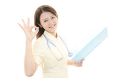 Asiatisk kvinnlig sjuksköterska med det ok handtecknet Royaltyfria Bilder