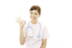 Asiatisk kvinnlig sjuksköterska med det ok handtecknet Fotografering för Bildbyråer