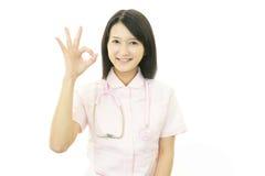 Asiatisk kvinnlig sjuksköterska med det ok handtecknet Arkivfoton