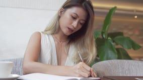 Asiatisk kvinnlig student som lär engelskt språk lager videofilmer