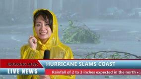 Asiatisk kvinnlig TVväderreporter som anmäler den dåliga stormen arkivfilmer