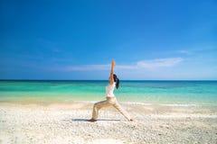 Asiatisk kvinnlig utförande yoga på en strand Arkivbild