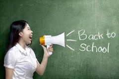 Asiatisk lärarekvinna som använder megafonen för att meddela för för att gå tillbaka till skola med svart tavlabakgrund arkivbild