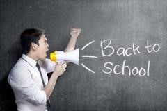 Asiatisk lärareman som använder megafonen för att meddela för för att gå tillbaka till skola med svart tavlabakgrund royaltyfria foton