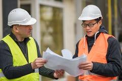 Asiatisk lärlingtekniker på arbete på konstruktionsplats med den höga chefen Royaltyfri Fotografi