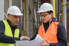Asiatisk lärlingtekniker på arbete på konstruktionsplats med den höga chefen Arkivbilder