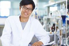 Asiatisk laboratoriumforskare som arbetar på labbet med provrör Arkivbild