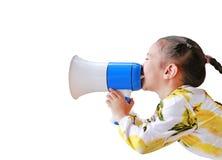 Asiatisk liten flicka att meddela vid megafonen som isoleras p? vit bakgrund med kopieringsutrymme svart telefon f?r kommunikatio royaltyfri foto