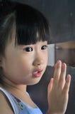 Asiatisk liten flicka i överraskningblick ut fönstret Arkivbild