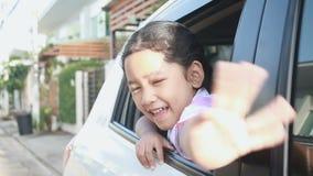 Asiatisk liten flicka i rörelse för hand för flyttning för thailändskt studentdagis enhetlig med leende och lycka i bilen med den lager videofilmer