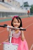 Asiatisk liten flicka och cykel Arkivfoto