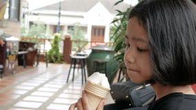 Asiatisk liten flicka som äter glass med djup för vald fokus för lycka grunt av fältet lager videofilmer