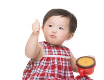 Asiatisk liten flicka som äter mellanmålet med tummen upp Arkivfoton