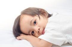 Asiatisk liten flicka som hemma ligger på sängen Arkivfoto