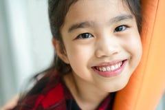 Asiatisk liten flicka som ler med perfekt leende och vita tänder i tandvård arkivbild