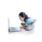 Asiatisk liten flicka som spelar lekar med bärbar datordatoren, och joystic Arkivbilder
