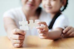Asiatisk liten flicka som spelar pusslet med hennes moder för fami arkivbild
